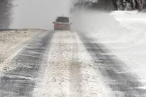 Automobil jede po zasněžené silnici. Ilustrační foto.
