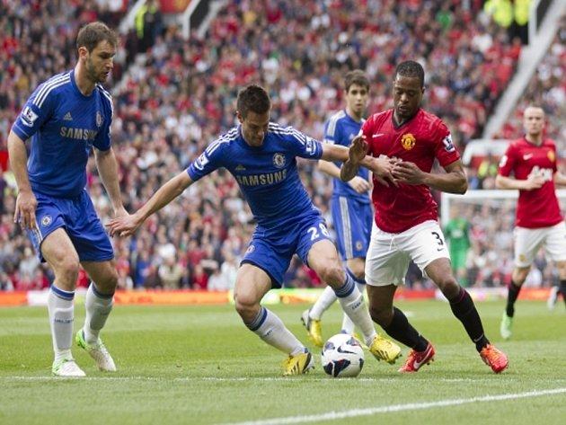 Cesar Azpilicueta z Chelsea (uprostřed) si zpracovává míč před Patricem Evrou z Manchesteru United.