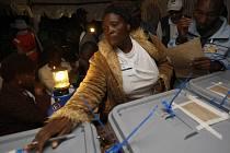 Členka volební komise kontroluje urny s odevzdanými hlasy.