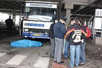 Řidič autobusu zemřel za volantem na autobusovém nádraží v Mladé Boleslavi. Na fotografii policie zjišťuje svědectví školáků, kteří přivolali pomoc.
