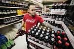 Pracovník obchodu skládá Coca-Colu do regálů.