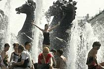 Lidé se chladí ve fontáně v moskevské Alexandrovské zahradě.