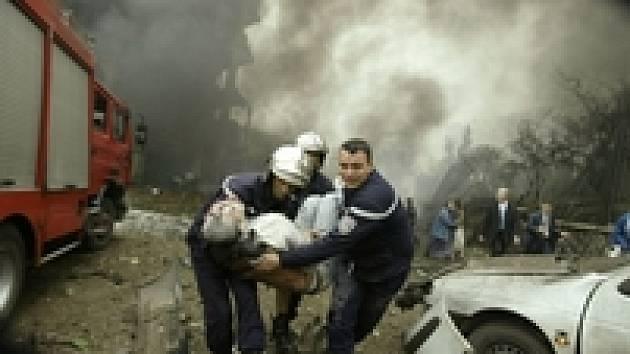 Hasiči vynášejí zraněného muže nedaleko vládní budovy