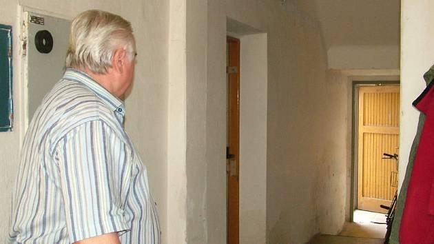 Jan Štastný ze sousedního domu míří ke dveřím (vlevo) za nimiž ležela několik let mrtvola.