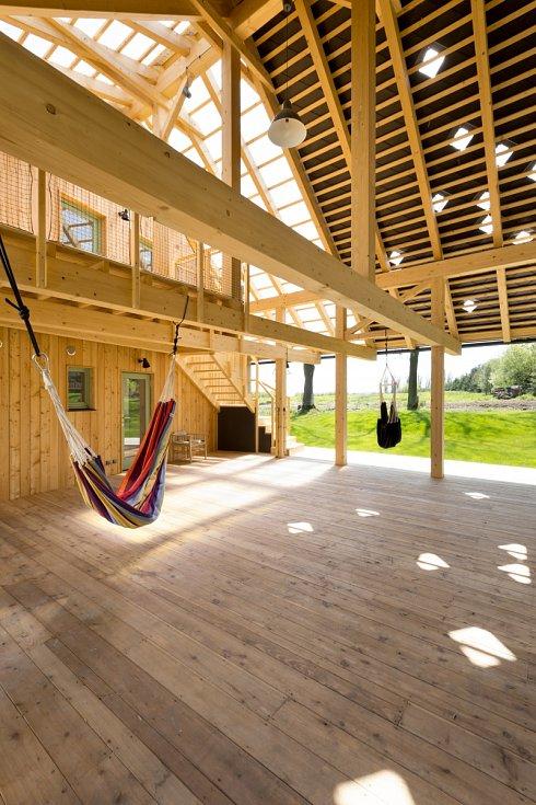 Nový dům sice dvůr uzavírá, ale zároveň umožňuje široký průhled otevřeným středem přízemí. Svou formou se podobá tradiční dřevěné stodole s otevřeným průjezdným mlatem.