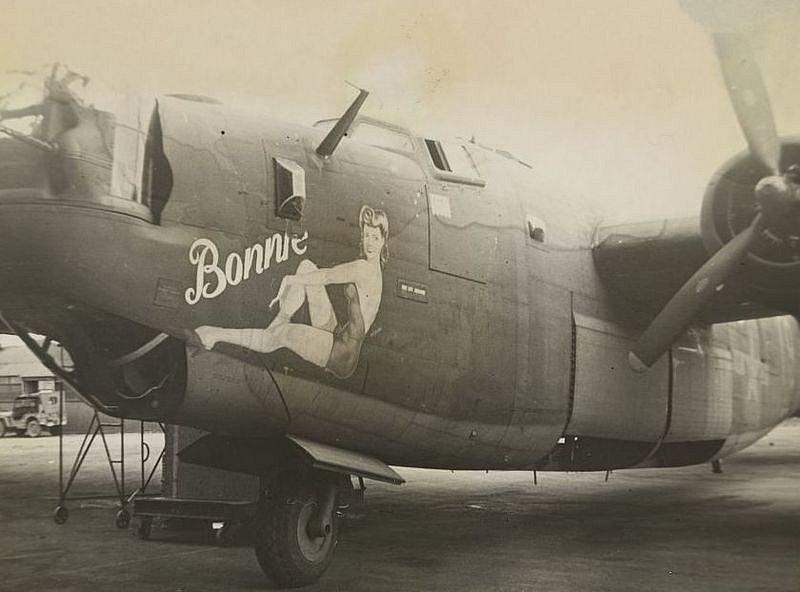 Desátník J. S. WIlson zdobí smyslnou malůvkou bombardér B-24.