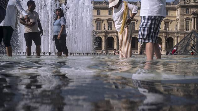 Lidé se v horkém letním počasí osvěžují ve fontáně v pařížském Louvre.