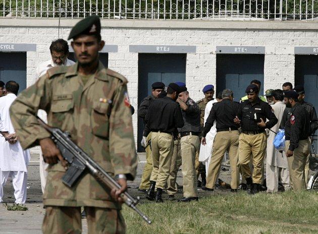Pákistánští policisté střeží budovu muniční továrny ve městě Wáh, kde se včera odehrál dvojí pumový útok.
