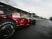 Mechanici Ferrari vymetají vodu z boxů svého týmu po páteční průtrž mračen nad okruhem v Monze.