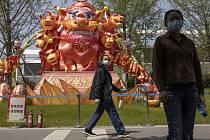 Lidé v rouškách v parku v čínském Wu-chanu, 9. dubna 2020