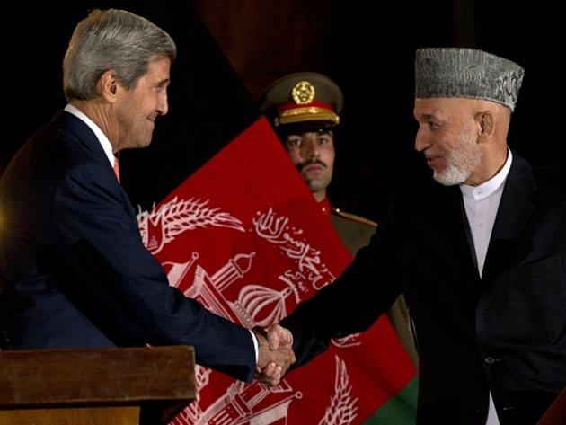 Americký ministr zahraničí John Kerry (vlevo) a afghánský prezident Hamíd Karzáí dosáhli předběžné bezpečnostní dohody, jejíž součástí je i další působení části ozbrojených sil USA v Afghánistánu.