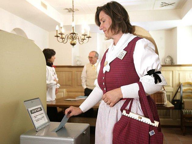 Žena v tradičním kostýmu hlasuje ve volební místnosti v gersau ve středním Švýcarsku.