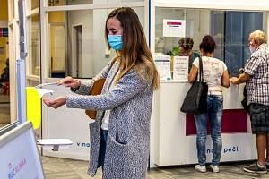 Žena si dezinfikuje ruce ve vstupním prostoru ústecké polikliniky na snímku z 24. července 2020
