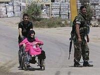 Žena na invalidním vozíčku opouští kvůli bojům tábor Nahr Bárid.
