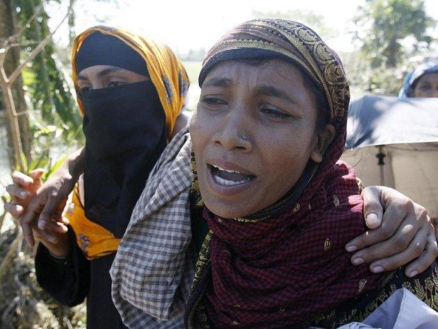 Žena oplakává svou matku, která se ztratila během ničivé bouře.