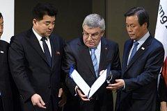 Prezident Mezinárodního olympijského výboru Thomas Bach (uprostřed) se zástupci KLDR a Jižní Koreje.
