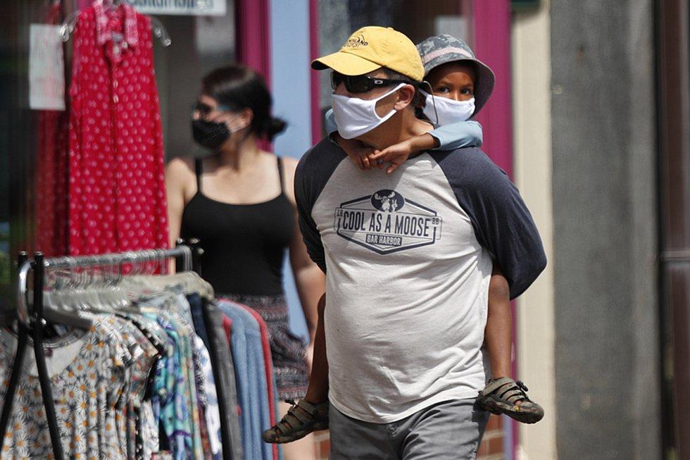 Muž v roušce s dítětem na zádech míjí 25. července obchod s oblečením v americkém městě Bath