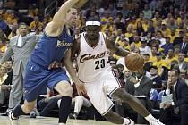 Clevelandský Rytíř LeBron James se snaží proniknout obranou Washingtonu v podání Dariuse Songaila.