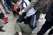 Demonstranta za svobodu Tibetu z České republiky mlátí muž v teplákové soupravě, který běžel v konvoji s olympijskou pochodní.