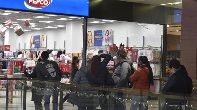 Zákazníci čekají 6. prosince 2020 před jedním z obchodů v Galerii Harfa v Praze