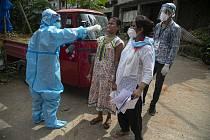 Zdravotníci provádí testování členů domácností na nemoc covid-19 v indickém městě Gauhátí.