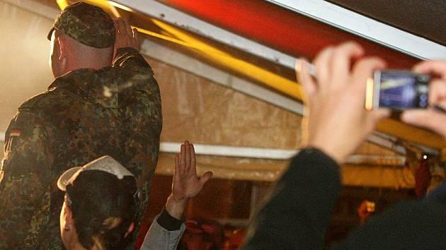 Vysoký muž s pěchotní čepicí v uniformě od Bundeswehru si stoupá na lavičku a vztyčuje pravici.