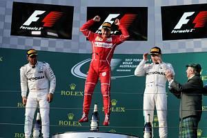 Sebastian Vettel (uprostřed) slaví triumf ve Velké ceně Austrálie. Druhý dojel Lewis Hamilton (vlevo) a třetí byl Valtteri Bottas.