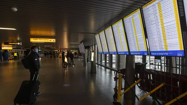 Cestující v roušce na letišti Schiphol poblíž nizozemského Amsterdamu