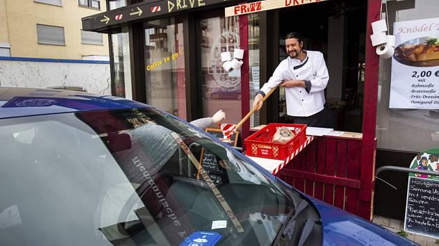 Pekař ve Weilu na Rýnu podává zákazníkovi pečivo do auta v improvizovaném drive-in provozu
