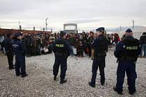 Maďarští policisté dohlíží na migranty čekající na vlak do Srbska.