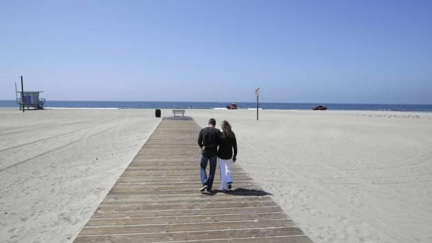 Manželský pár na prázdné pláži Santa Monica v Los Angeles 29. března 2020