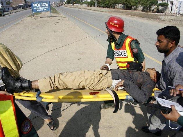 Záchranáři vynášejí zraněného kadeta z policejní akademie v pákistánském Láhauru.