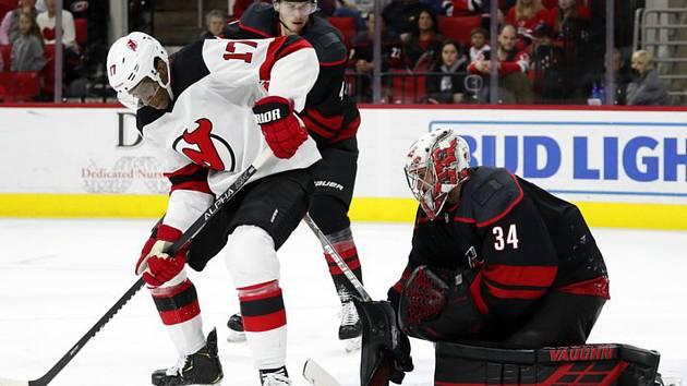 Hokejista New Jersey Devils Wayne Simmonds se snaží dostat puk za záda brankáře Caroliny Hurricanes Petra Mrázka.