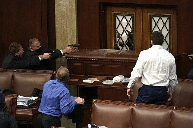 Ochranka Kapitolu míří zbraněmi na zabarikádované dveře u jednacího sálu, kam chtějí vtrhnout demonstranti.