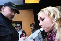Dívka fouká do alkomatu, zda nepožila zakázaný nápoj. Ilustrační foto.