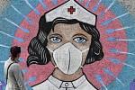 Žena se dívá 13. dubna 2020 v německém Hammu na graffiti pouličního umělce jménem Uzey. Malba zobrazuje zdravotní sestru s obličejovou maskou, na kterou útočí koronavirus v podobě šípů