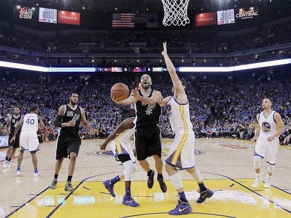 Tony Parker ze San Antonia (uprostřed v černém) se snaží skórovat, brání mu Andrew Bogut z Golden State Warriors.