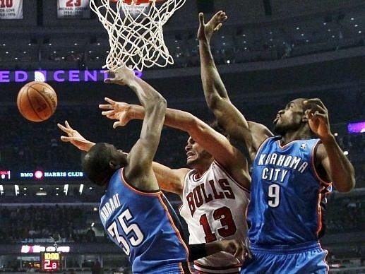 Kevin Durant (vlevo) a Serge Ibaka z Oklahomy brání ve skórování Joakimu Noahovi z Chicaga.