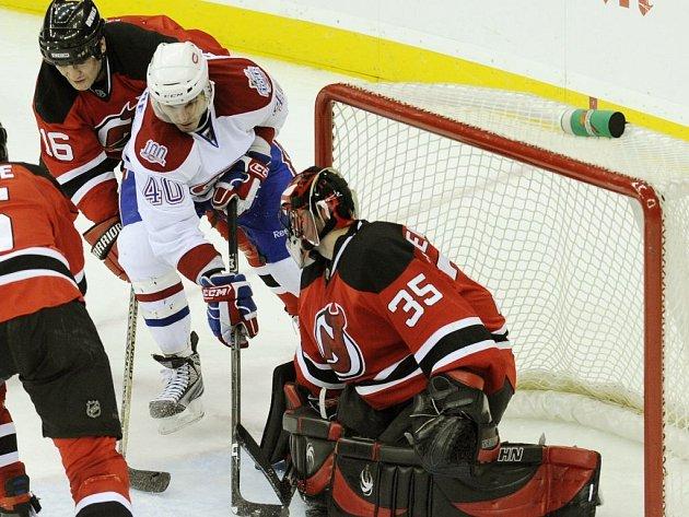 Střední útočník Montrealu Canadiens Maxim Lapierre (č. 40) se snaží propasírovat puk skrz betony brankáře New Jersey Devils Scotta Clemmensena. Tomu se snaží pomoci Bobby Holík.