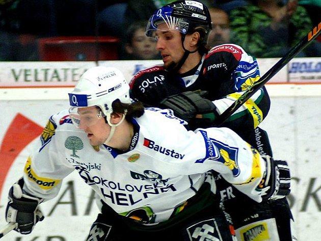 Mladoboleslavský obránce Jindra bojuje o puk s karlovarským Hluchým.