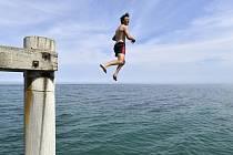 Plavec skáče do moře z mola v australském přístavu Port Noarlunga v Adelaide.