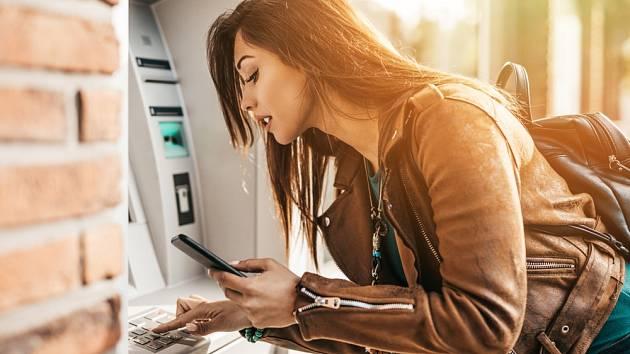Žena vybírá hotovost z bankomatu