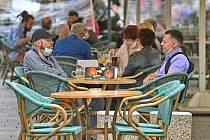 Lidé na zahrádce restaurace v Brně