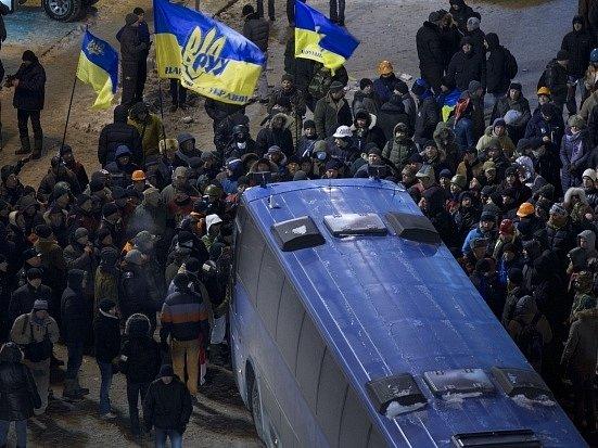 Demonstranti se snaží zablokovat policejní autobus.