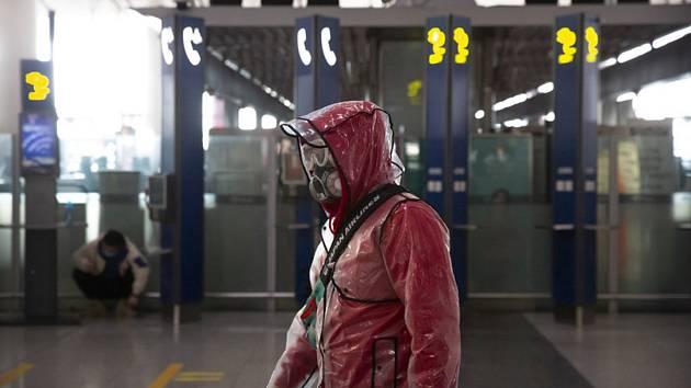 Cestující v respirátoru a pláštěnce na letišti v Pekingu 28. března 2020