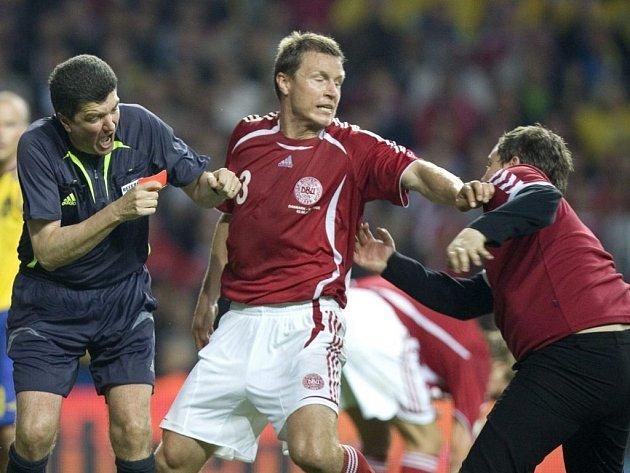 Dánský fotbalista Michael Gravgaard brání sudího Herberta Fandela před rozzuřeným fanouškem.
