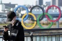 Turista v roušce v Toliu na snímku ze 3. března 2020, v pozadí olympijské kruhy