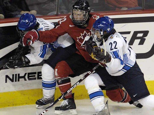 Kanaďanka Hayley Wickenheiserová (uprostřed) v obležení dvou finských hráček, Jenni Hiirikoskiové (vlevo) a Saari Tuominenové.