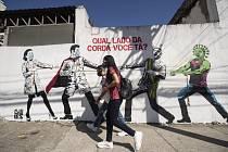Žena v roušce prochází 19. června 2020 v Sao Paulu kolem nástěnné malby, která zobrazuje přetahovanou mezi zdravotníky a brazilským prezidentem Jairem Bolsonarem za pomoci kreslených postaviček.