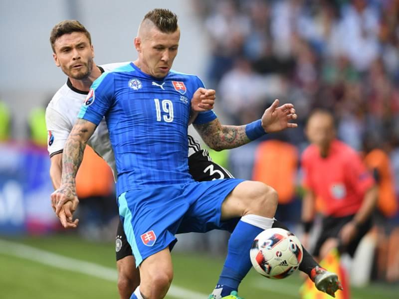 Juraj Kucka ze Slovenska (vpravo) si zpracovává míč před Jonasem Hectorem z Německa.